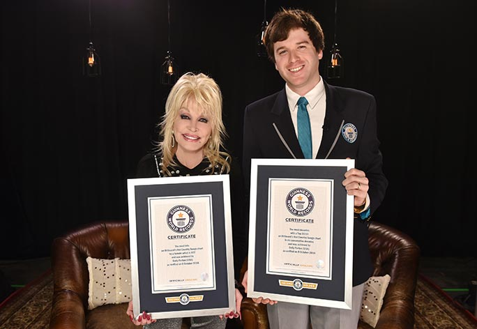 Dolly Parton receives her certificates from an official Guinness World Records adjudicator
