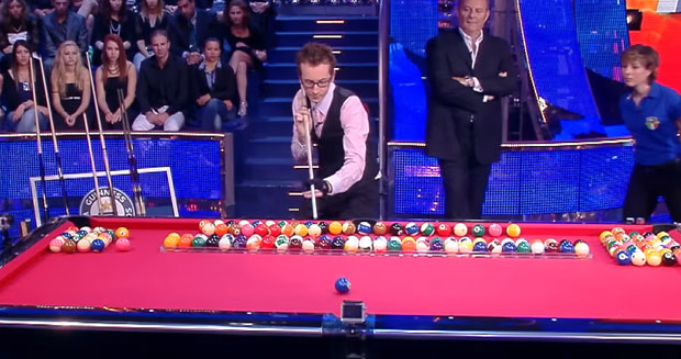 Most pool balls potted into the middle pocket over an obstacle in one minute