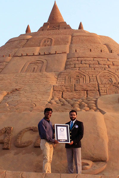 GWR judge Swapnil presents a certificate to Sudarsan in front of the record-breaking sandcastle