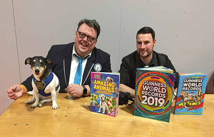 GWR's Editor-in-Chief Craig Glenday (left) and Animals Editor, Adam Millward (right), at the National Pet Show in 2018, signing books alongside record-breaking Jack Russell Jessica