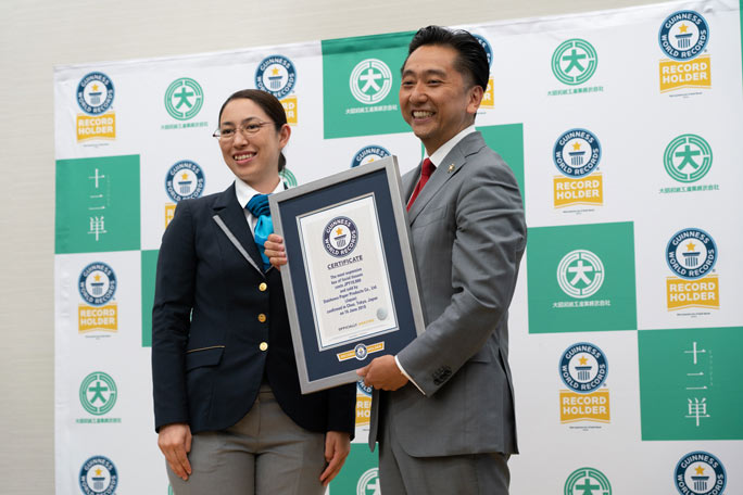 Ryosuke Saitoh, the president of Daishowa Paper Products, receiving the official certificate