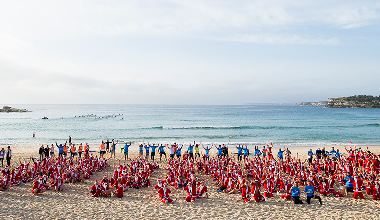 Hundreds of Aussies dress as Santa to take part in largest surfing lesson