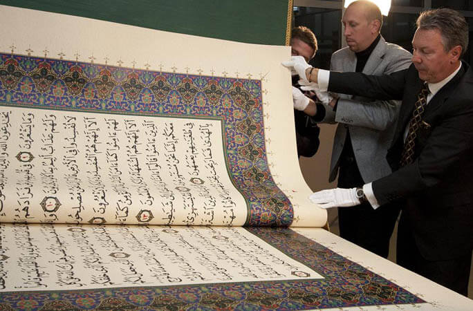 Men exploring pages of the largest Quran