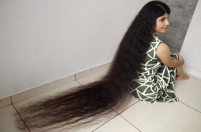 Nilanshi Patel sitting on the floor with hair spread out
