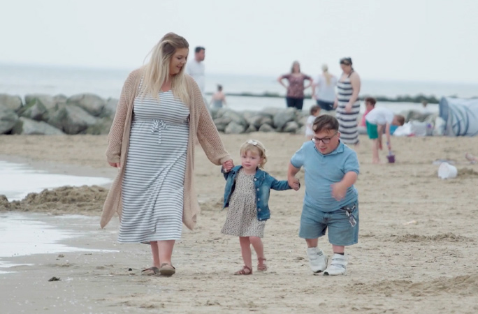 james and chloe walking across the beach with daughter olivia