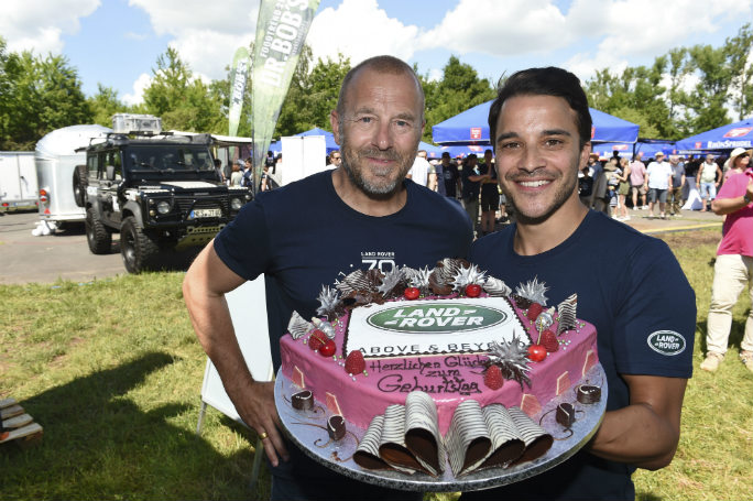 Actors Heino Ferch and Kostja Ullmann with the Land Rover anniversary cake