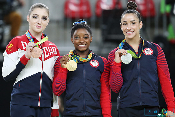 Simone shows off her gold medal for the women's individual all-around final at Rio 2016. She is flanked by compatriot Alexandra Raisman (silver) and Aliya Mustafina (bronze) of Russia