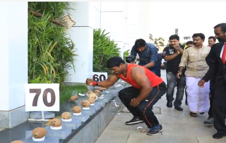 Most coconuts smashed with one hand in one minute