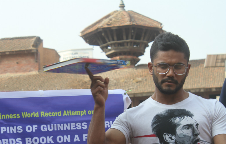 Most spins of a Guinness World Records book on the finger in one minute